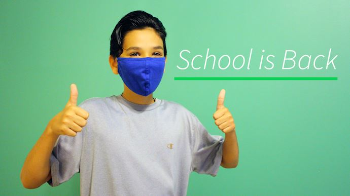 A school aged boy wearing a face covering and gesturing thumbs up