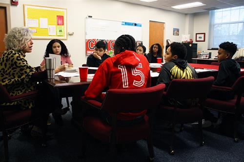 middle school students seated at a table and listening to an adult femaile