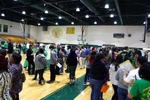 Students, parents and high school teachers talking in a high schools gym
