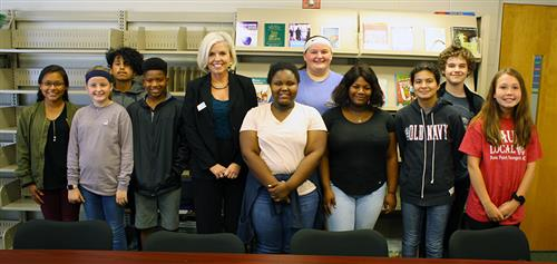 Ten middle schools students stand and pose with an adult female in a black business suite