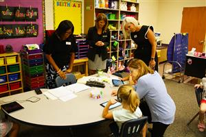 Four adult ladies watch as two elementary school student work at a table