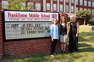 Three adult females pose in front of a brick sign for Franklinton Middle School