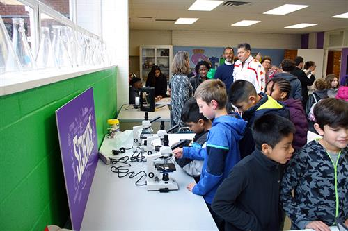 A group of students surround microscopes in a STEAM lab