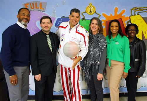 Five adults with a Harlem Globetrotter at a STEAM Lab