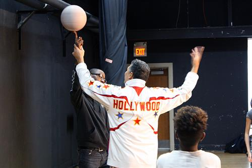 A Harlem Globetrotter helps a student spin a basketball on his fingertip