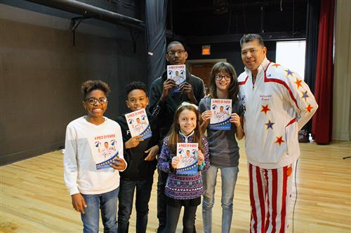 Five students hold up books and pose with a Harlem Globetrotter