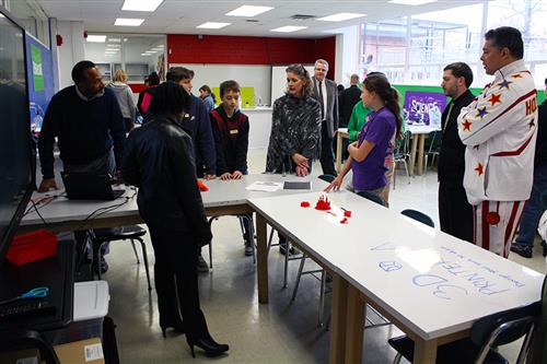 A group of adults and students in a STEAM lab at the 3D printer display