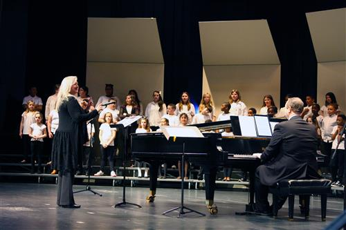 A conductor and pianist in front of a school choir