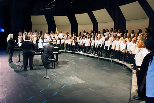 135 elementary students dressed in black pants and white shirts on stage as a chorus