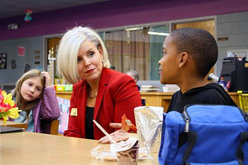 An adult talks with an elementary school student at a table as another student observes