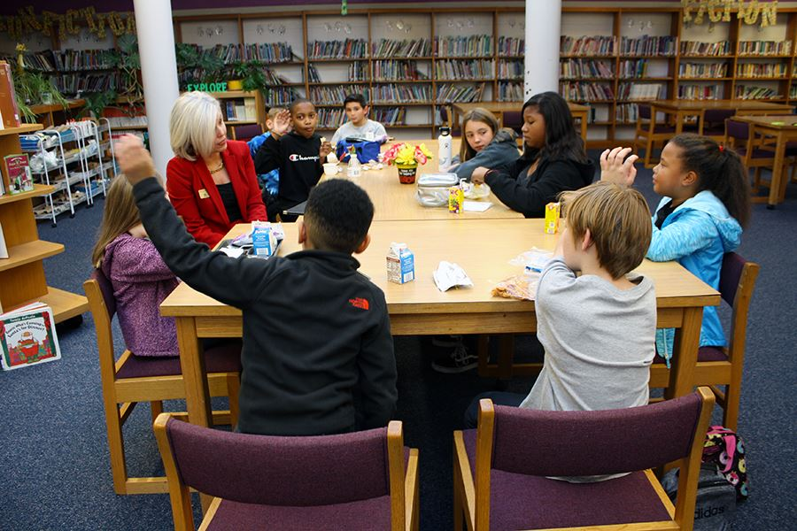 The superintendent of Franklin County Schools sits at a table with 9 elementary school students