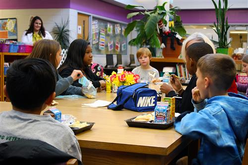 Seven elementary school children sit at a table and eat lunch as an adult female watches and another talks