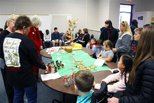 Elementary school students and adults around a table full of holiday crafts