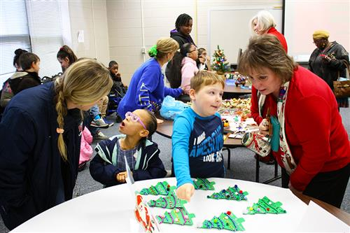 Customers listen as students describe the holiday crafts on a table