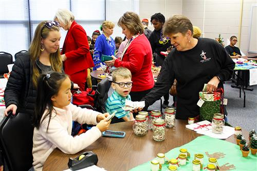 A customer makes a purchase of holiday crafts from student salespeople