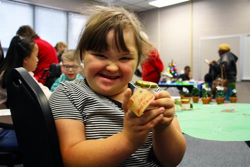 An elementary school students smiles and shows her handmade holiday craft