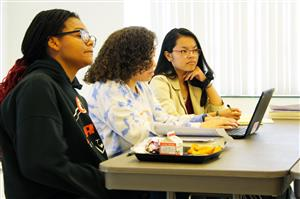 three femaile high school students are seated at a table and listening