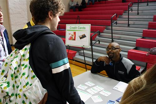 A counselor is seated at a table having a discussion with a male high school student about credit cards