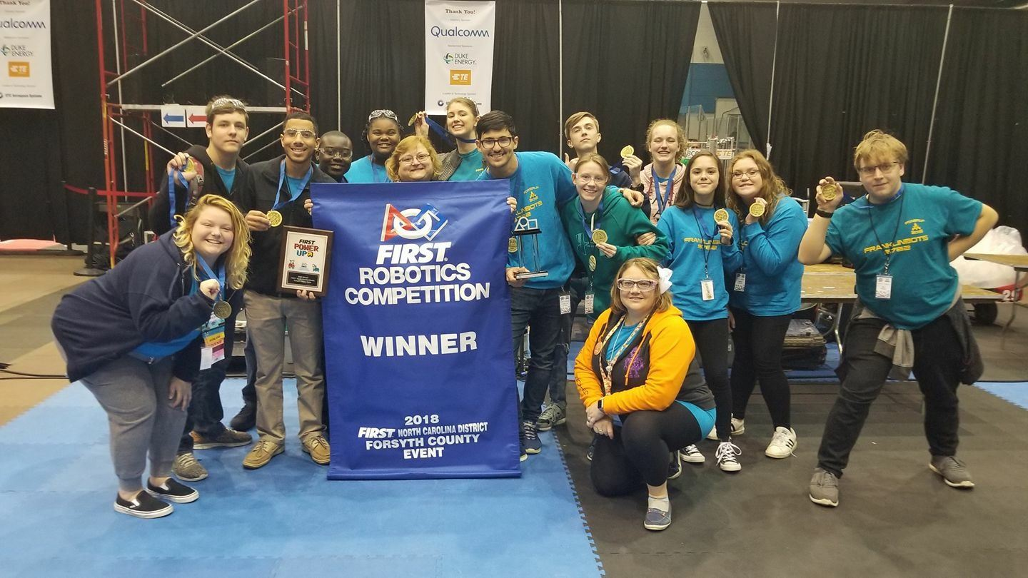 Robotics team holding a banner showing their big win.