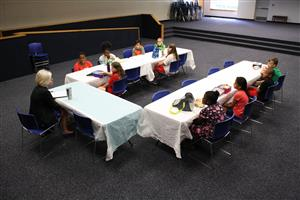 10 elementary school students seated around two tables