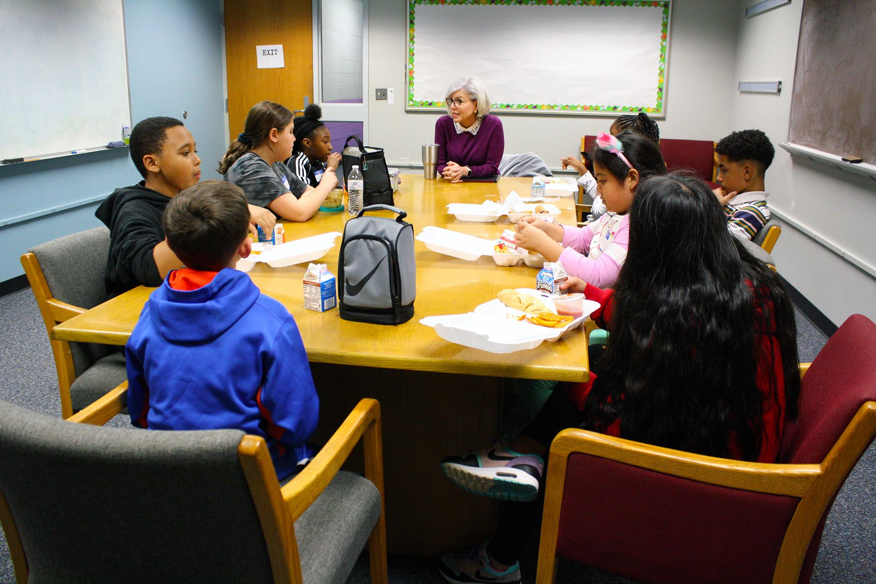 Eight elementary school students seated at a table eating lunch and talking with an adult female