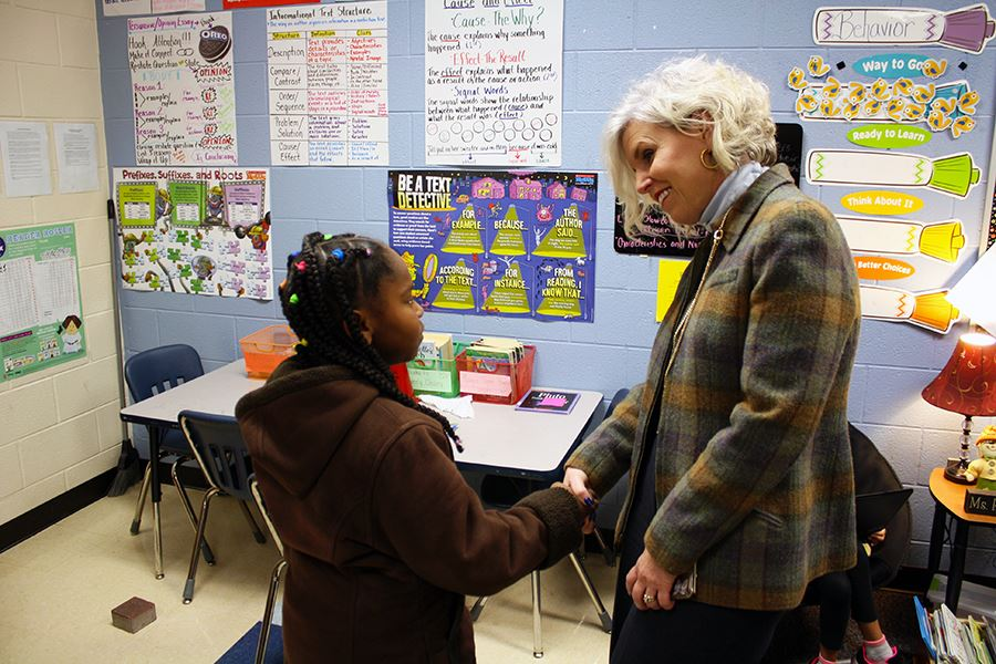 An elementary school girl shakes hands with an adult female