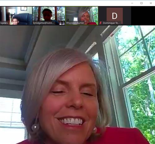 a screen shot of an adult female on a video call with elementary students