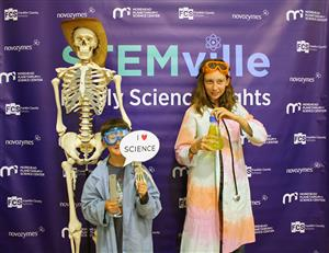two young students dressed in science clothing stand in front of a purple banner beside a skeleton wearing a cowboy hat.