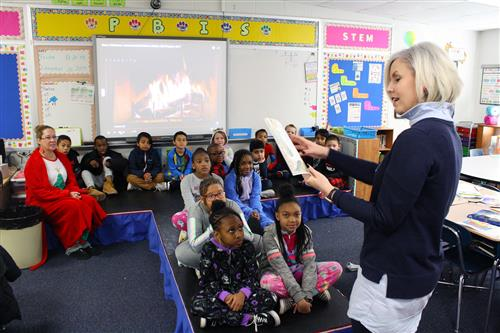 An adult female reads a book to students