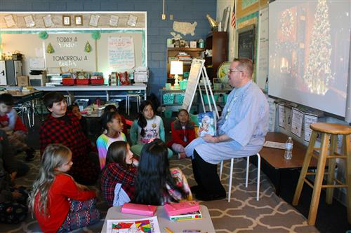 An adult male reads to a classroom of students