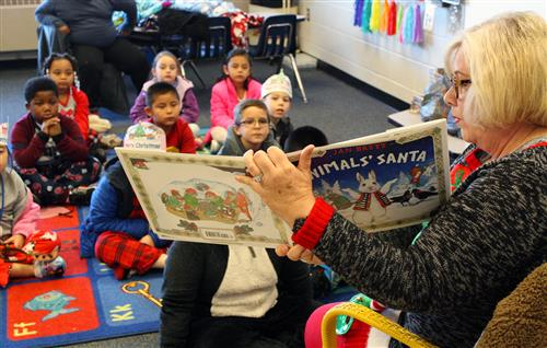 An adult female reads a book to elementary school students