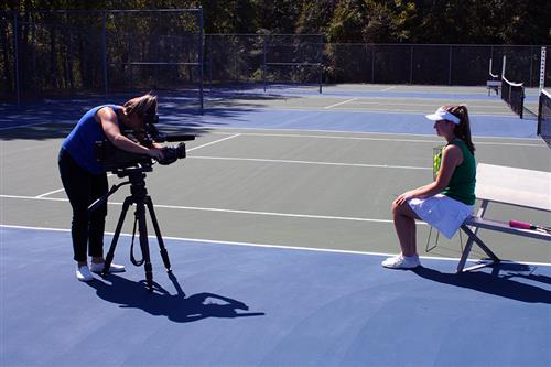 A TV photojournalist with camera pointed at a female high school on a tennis court